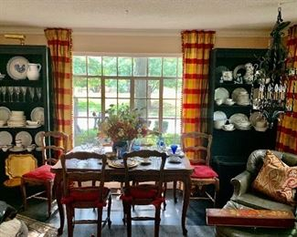A view of the other end of the living room featuring a French reflection table, a set of six side chairs, several sets of china, stemware and more!