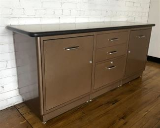 "Beautiful modern credenza by All-Steel Furniture, Aurora IL. Original ""chocolate brown"" finish and ""wheat"" top. Lots of great storage with 2 cabinet doors, and 3 drawers. Bring this modern collector's piece to your home or office. Super clean with a couple minor scratches. No dents or dings. 68"" x 29.5"" x 18"""