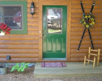 Antique skis & seasonal wreaths, small pine log chair