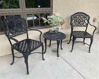 Iron patio chairs and side table with metal fish statue