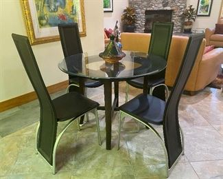 Unusual modern glass table with four black leather chairs