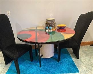 Modern round table and black upholstered chairs, table signed by artist