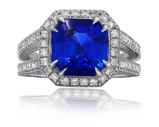 A SAPPHIRE AND DIAMOND RING Impressive 3.98 carat sapphire set on an 18K split shaft ring, the stone prong-mounted and accented by 1.2 carats of round white diamonds comprising the halo and and set into the band.
