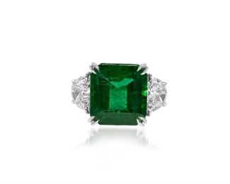 AN EMERALD AND DIAMOND RING Attractive 9.79 carat emerald and diamond ring, the 9.79 carat central stone set with half-moon diamonds on either side totaling 1.68 carats in a platinum setting.