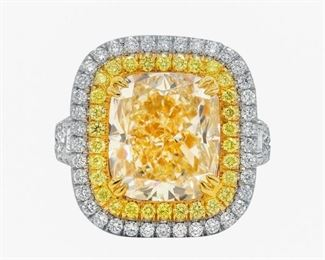 A FANCY 7.03 CARAT YELLOW DIAMOND RING A magnificent fancy yellow diamond ring featuring a cushion cut 7.03 carat diamond graded FLY VVS, mounted in platinum with a double halo setting of yellow and white diamonds, with two additional pear cut diamonds set in the split shank. A total of 1.90m carats of diamonds, in addition to the large central stone. With EGL colored diamond certificate.