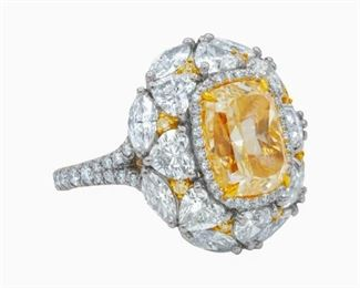 A YELLOW AND WHITE DIAMOND RING, 10.01 CARATS Platinum and 18K gold fancy light yellow diamond ring, the central stone 5.01 carats and GIA certified (RADC945), set with marquise and heart-shaped white diamonds, and yellow round diamonds all around, adding another 5.00 carats in diamonds to this creation. Set in 18K white gold. With GIA certificate.