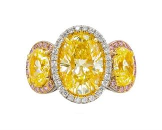 A YELLOW DIAMOND RING Custom designed triple yellow diamond ring featuring a center fancy yellow 4.52 carat oval brilliant cut diamond (OVC230, SI1), further enhanced by the addition on either side of similarly-cut fancy yellow diamonds, 2.30 total carats, VS1 clarity. These stones are presented in pave settings of .75 carats pink and white diamonds, F-G color, VS. With EGL certificate for central stone. Natural untreated diamonds, the other white diamonds near colorless white, slightly included. EGL CERTIFICATE #US 313590601D