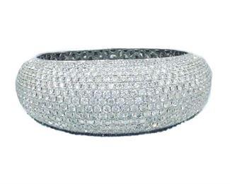 A DIAMOND BANGLE BRACELET, 35.00 CARATS Diamond bangle bracelet displaying 35.00 carats of diamonds set half the way around the 18K white gold cuff. Natural untreated diamonds, near colorless white, slightly included.