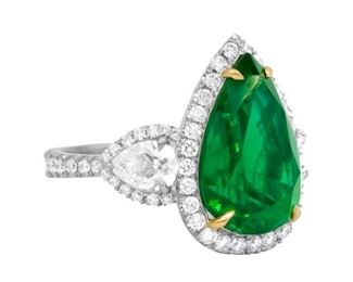 AN EMERALD AND DIAMOND RING Custom made green emerald and diamond ring, displays a 8.78 carat pear-shaped green emerald at center with two pear-shaped GIA certified diamonds on either side, all three stones surrounded by micropave round diamonds totaling 2.00 carats. The emerald is cleverly secured with yellow 18K gold prongs, the ring itself in platinum. Spectacular. With C. Dunaigre Laboratory emerald certificate and two GIA diamond certificates. Other diamonds are natural untreated diamonds, near colorless white, slightly included. GIA CERTIFICATE #1215069844 : #5133661067 C. DUNAIGRE CERTIFICATE #CDC 1711567