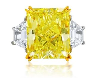 A YELLOW AND WHITE DIAMOND RING Magnificent fancy yellow diamond engagement ring, the center stone a radiant cut 10.03 carat fancy yellow diamond, GIA certified FCY-SI1 (RADC1028). The stunning yellow diamond is mounted with complimenting 18K yellow gold prongs, and it is surrounded on either side with two-step trapezoid diamonds, 1.21 carats total, these set in the platinum band. With GIA certificate for the central stone. Natural untreated diamonds, the white diamonds near colorless white, slightly included. GIA CERTIFICATE #2185299700