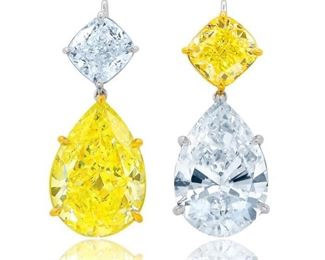 """A PAIR OF YELLOW AND WHITE DIAMOND EARRINGS A unique, magnificent pair of yellow and white diamond earrings, a simply spectacular combination. This presentation combines lower suspended pear-shaped stones including a 15.91 carat Fancy Intense Yellow diamond and a 14.73 carat White F, VS2 White diamond. Each is cleverly complemented above by a stone of an """"opposite"""" color, cushion-cut diamonds of 4.00 carats each, including a Fancy Intense Yellow diamond, (VS, E) and a White Diamond, (E, VS-2). With four GIA certificates for the large stones. Brilliant! GIA CERTIFICATE #5172889549 : #5182082634 : #17445098 : #2155330196"""