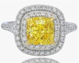 YELLOW AND WHITE DIAMOND RING Distinctive yellow and white diamond ring, presents at center a fancy light yellow cushion cut diamond, GIA certified 2.01 carats FLY-VVS2, set in a double halo of 0.65 carats of white round diamonds with additional diamonds on the shank. Natural untreated diamonds, the white diamonds near colorless white, slightly included unless specified otherwise.