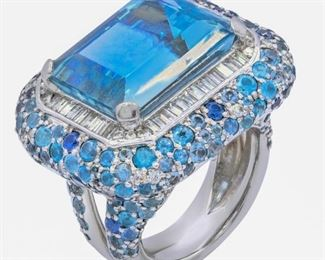 AN AQUAMARINE AND DIAMOND RING Aquamarine and diamond ring, displays a gorgeous 20.00 emerald-cut surrounded by 1.50 carats of white baguette diamonds and a perimeter of additional aquamarines, the entirety set into 14K white gold. Natural untreated diamonds, the white diamonds near colorless white, slightly included unless specified otherwise.