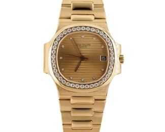 """PATEK PHILIPE YELLOW GOLD NAUTILUS Patek Philipe Nautilus women's yellow gold watch, cushion-shaped 27mm. case, 6mm. thick, the dial surrounded by a ring of diamonds. Champagne dial with diamond markers, matching gold bracelet for a 5"""" wrist. Quartz movement. 1984. Patek Philipe #4700. Water resistant to 60m."""