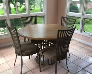 "Solid wood top. Wrought iron base with 4 matching chairs. Table top diameter is about 37"". Made by Johnston Casuals Co. who are known for a more modern or contemporary style."
