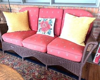 One of two, antique brown wicker sofas