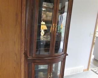 """Lighted curved glass curio cabinet (one-piece). 77"""" tall x 34"""" wide x 12"""" deep. PRICE: $225.00"""