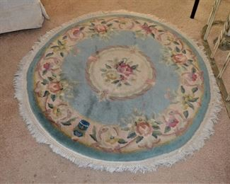 ONE OF SEVERAL SMALL ROUND RUGS