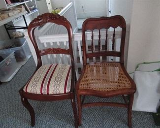 set of spindle back chairs with caned seats.  Carved crest on other chair.