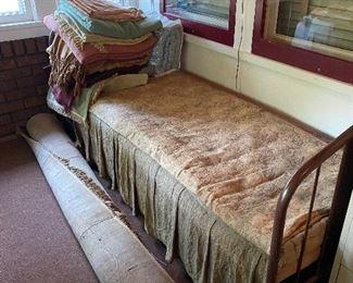 Antique bed, blankets, area rug