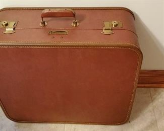 leather suitcase has hanging area inside.