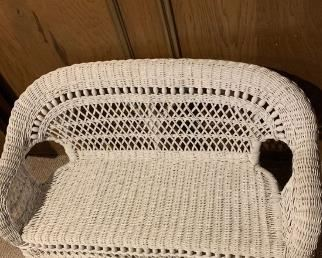 Charming, white wicker bench for children. This item is made from authentic wicker, and has no plastic or man made materials. Wooden beadwork alone back. Perfect condition. Dimensions 36Lx17Dx21H.