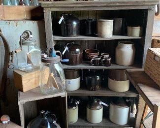 Antique crocks, primitive jugs, vintage butter churns, primitive cupboard, old barn pulley, antique bottles