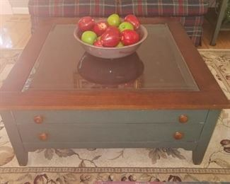 Square glass top coffee table, with two drawers.  One of the three piece set.