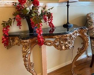 Gilded gold, marble top table-mounts to wall.