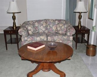 """Antique Empire Style Oak Round Pedestal Table.  Table has been mortified from a dinning table to a cocktail/coffee table.(42""""D x 18""""H). Vintage Hepplewhite Mahogany End Tables with single drawer (24""""H x 16""""W x 23.5""""D).  Also shown Hamilton House Tapestry Floral Upholstered Sofa/Loveseat and a pair of Heavy Brass Table Lamps"""