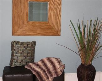"""Bombay Company Bevel Rattan Framed Bevel Mirror (35.3"""" x 35.5"""") shown with Worldwide Cappuccino Faux Leather Cube Ottoman (18"""" x 18"""").  Brown Rattan Vase (19""""H) with Wild Reeds & Grasses"""