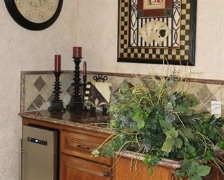 """View of wet bar displaying; Silk Green Arrangement, Fleu De Lis Decor Tile,  Westgate Candle Stands and Bombay Co 24"""" World Time Wall Clock"""