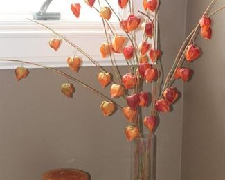 Orange Tone Pillar Candle on Wood Stand and Faux Orange Pod Floral Arrangement in Clear Cylindrical Glass Vase