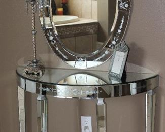 """Venetian Style Etched Mirrored Glass Demilune Table (29.5""""H x 40""""W x 17""""D) with Oval Mirror (26"""" x 56"""") shown with a Tall 36"""" Metal Candle Stick Lamp with Crystal Prisms and Square Cloth Shade and a Noble Elegance Venetian Collection 5 x 7 Frame"""