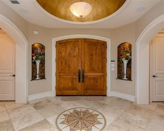 Entry View Facing Front Door Showing Tall White Blown Art Glass Trumpet Vases with Floral Arrangements.  (2 of 4 shown)