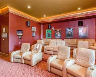 """Theater Room with Ivory Leather Theater Chairs.  Also shown are Movie Posters, including Batman, Spiderman,  Arnold Schwarzenegger """"Terminator"""", Lord of the Rings, etc. and Various Sports Prints, Posters and Photos"""
