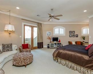 View of Upstairs Bedroom Suite with Kidney Shape Sof, Leopard Print Barrel Chair and Zebra Print Round Ottoman.  Queen Bed with Custom Silk Bed Set.