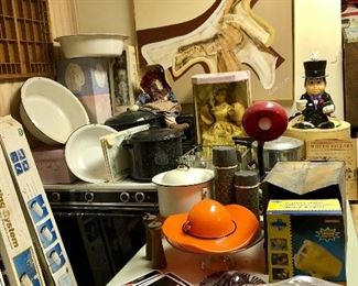 Abstract painting, enamel pans and pots, metal coke tags, orange glass hat, old thermos bottles, gas stove.