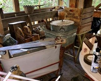 Back porch;  2 nice long wood benches , wooden crates,  galvanized square tub on stand, galvanized tub with lid, baby cradle(white in red frame, lots of hand saws all different sizes.