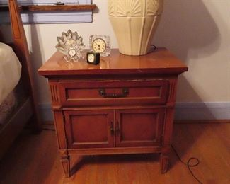 The matching night stand, cabinet below a drawer.