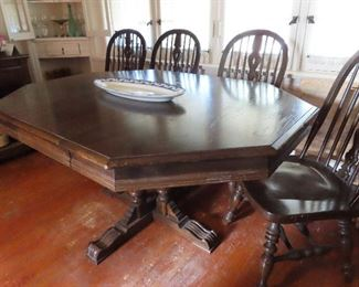 "THE TABLE, Octagon Shape,  Dark Charter Oak, on center carved pedestal ,  basic diameter  42"".  Two leaves 15"" each - overall length 72""  4 matching side chairs."