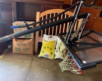 Basketball hoop includes base, pole, backboard, hoop