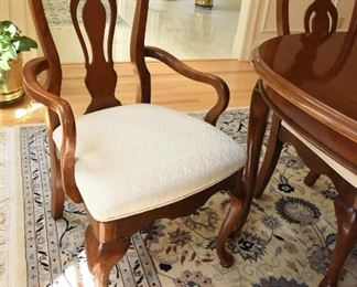 """Mahogany Dining Table with Eight Chairs  $350 Some sun fading on end closest to windows. Heat damage to top in two spots. Excellent candidate for refinishing or painting. Includes two armchairs and six side chairs. Chairs have off-white upholstery and some have spots. Table is 42"""" wide, 30"""" tall, and 65"""" long. There are two 15"""" leaves that extend the table up to 7'11"""""""