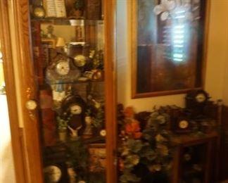 curio cabinet, owls, clocks, greenery
