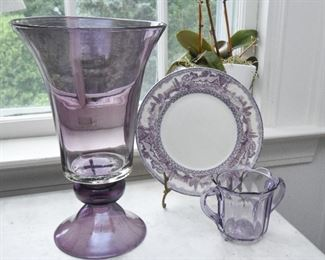 """Purple glass vase. Unsigned  $35 14"""" tall, 8.5"""" diameter. Hand blown, Bowl is attached with hot glass, not hand blown as a single unit Purple transferware plate, has a chip $5 Purple glass loving cup  $10 4.25"""" tall, 5.25"""" wide at handles. Chips along bottom edge"""