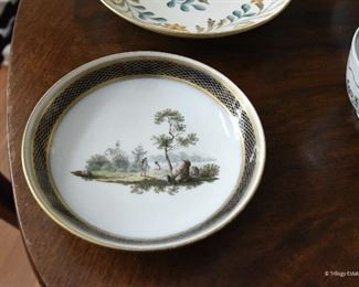 """5"""" round shallow dish  $12 Image of man hiking and one sitting on a log. cobalt blue and gold edging. Three faint Xs on the back"""