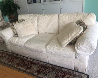 """Vanguard 88"""" rolled arm, 3-seat sofa with rope welt accent trim, in great condition.  Covered in tone on tone off-white stylized leaf pattern.  Rug with bk, burgundy, and neutrals."""