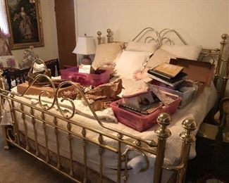 Brass bed minus items on top.