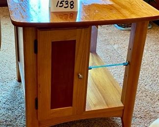"Lot 1538  $75.00 Maple Side Table w/ 1 Door in Front and Back, Glass Shelf, Maple and Cherry Veneers, The Top Surface shows wear and rough spots. Made by Riverside Furniture 26"" D x 22"" W x 24"" H"