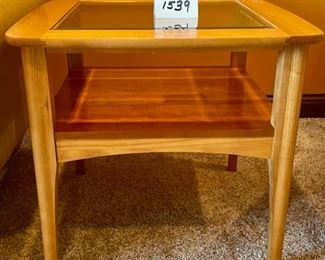 "Lot 1539  $105.00   Matching Side Table with 18"" Square Beveled Glass Top and Middle Shelf, Finished in Maple and Cherry Veneers, The Top Surface shows wear and rough spots by Riverside Furniture 26"" Square x 24"" H"
